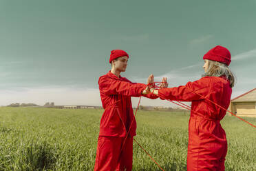 Young couple wearing red overalls and hats performing on a field with red string - ERRF03378