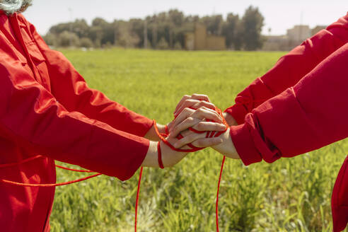 Crop view of young couple dressed in red performing on a field with red string - ERRF03381