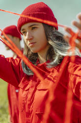 Portrait of young woman dressed in red performing with red string outdoors - ERRF03384