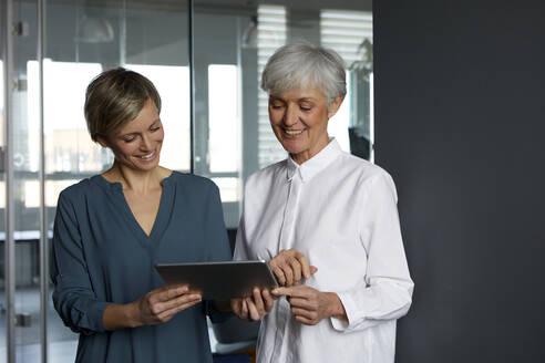 Two businesswomen sharing tablet in office - RBF07351