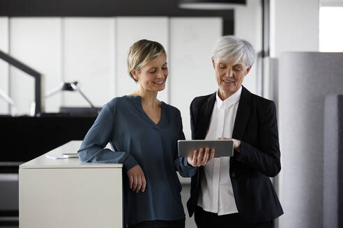 Two businesswomen sharing tablet in office - RBF07426