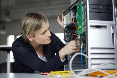Woman assembling desktop pc in office - RBF07450