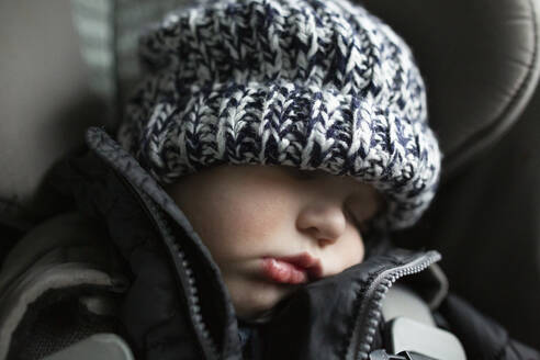 Close-up of toddler boy asleep in carseat while traveling in car - CAVF77998