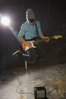 Teenage boy playing electric guitar, jumping above amplifier - FSIF04655