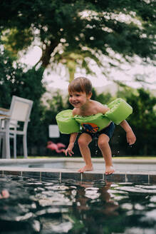 Little boy about to jump into a pool during the summer - CAVF78077