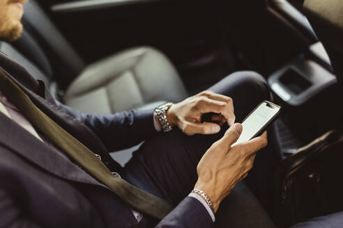 Midsection of businessman using device screen while sitting in car - MASF17611