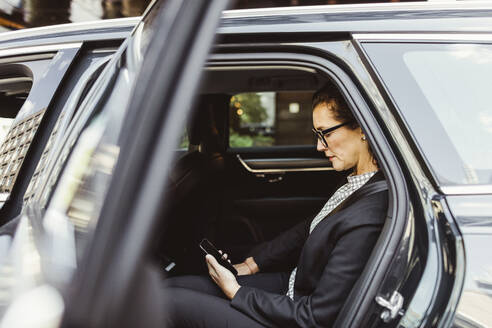 Entrepreneur using smart phone while sitting in car - MASF17614