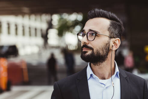 Confident businessman with in-ear headphones looking away while standing outdoors - MASF17647