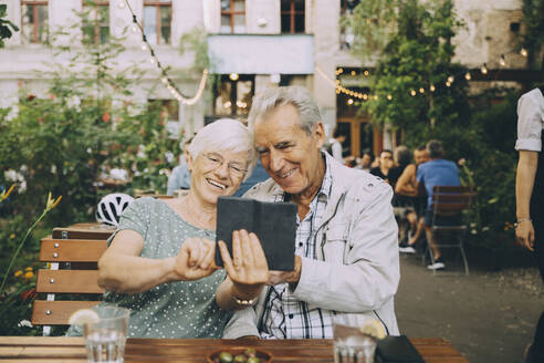 Smiling woman taking selfie with senior man while sitting at restaurant in city - MASF17677