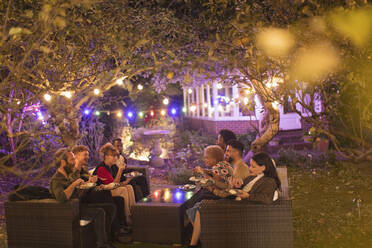 Friends talking and eating dessert under trees with string lights at garden party - CAIF26005