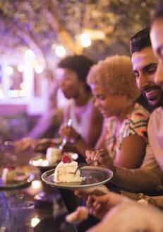 Friends eating dessert at garden party - CAIF26011