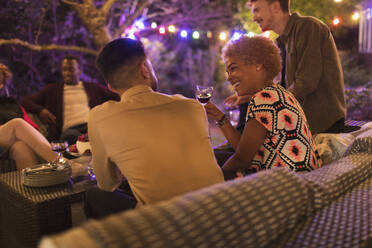 Friends drinking and talking at garden party - CAIF26014
