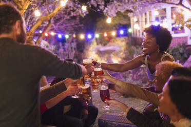 Happy friends toasting beer glasses at garden party - CAIF26020