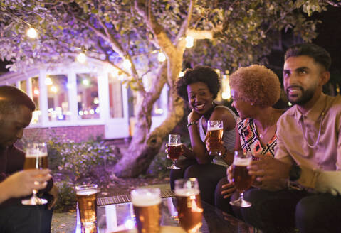 Friends talking and drinking beer at garden party - CAIF26026