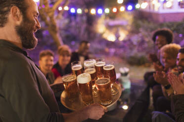 Man serving tray of beers to friends at garden party - CAIF26029