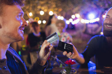 Man with credit card paying bartender at party - CAIF26035
