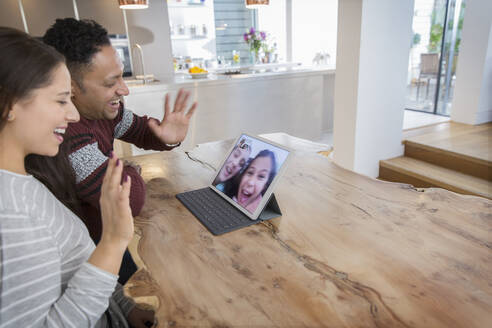 Happy parents video conferencing with daughters at digital tablet in kitchen - CAIF26194