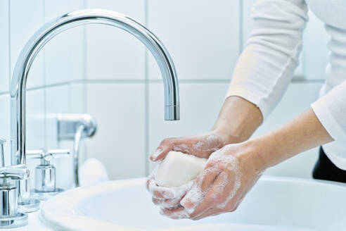 Woman washing her hand with soap - DIKF00410
