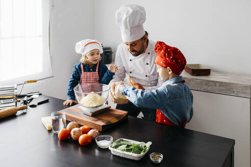Father with two kids preparing dough for homemade gluten free pasta in kitchen at home - JRFF04267