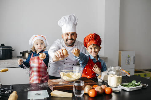 Portrait of father with two kids preparing dough in kitchen at home - JRFF04270