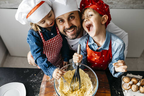 Portrait of happy father with two kids preparing dough in kitchen at home - JRFF04273