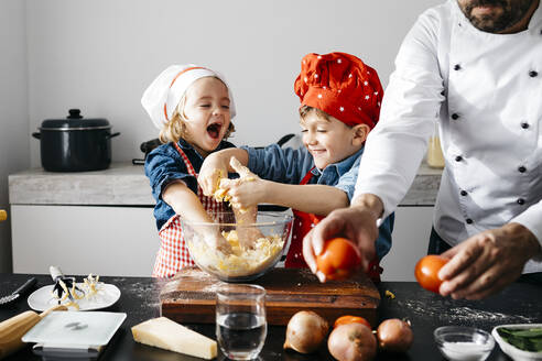 Happy kids preparing dough with father in kitchen at home - JRFF04276