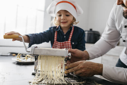 Father and daughter making homemade pasta with pasta machine in kitchen at home - JRFF04297