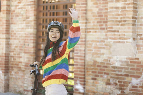 Asian student waving hello while holding e-scooter on sidewalk - CAVF78471