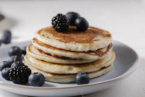 Stack of pancakes with berries on top on a white surface - CAVF78558