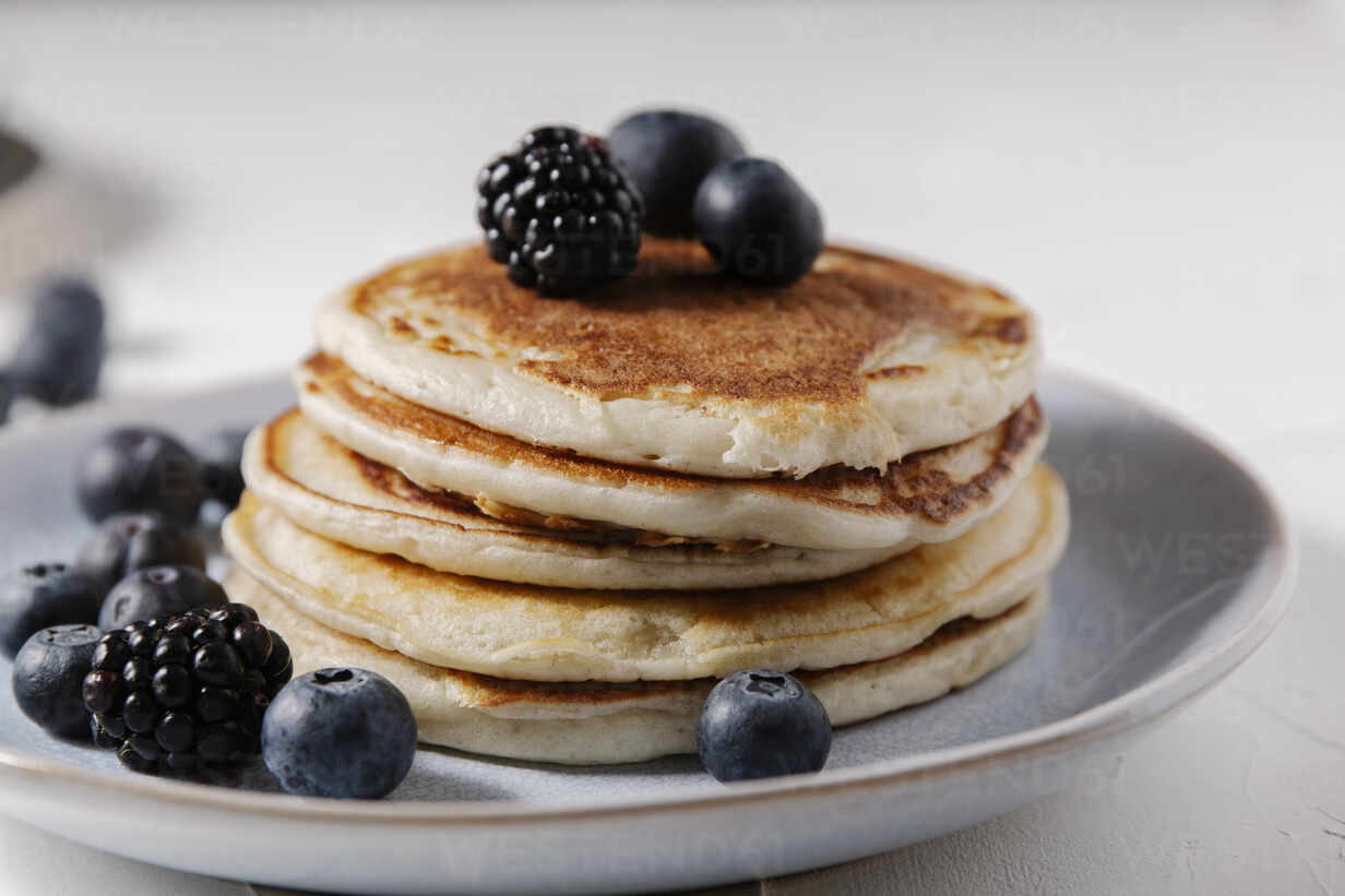 Stack of pancakes with berries on top on a white surface - CAVF78558 - Cavan Images/Westend61