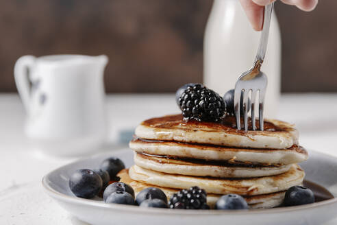 Woman sticking a fork into a stack of homemade pancakes - CAVF78561