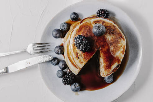 A stack of pancakes with berries and syrup - CAVF78570