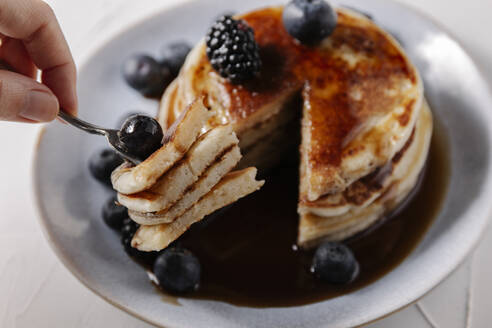 Woman sticking pancakes with a blueberry on a fork - CAVF78573