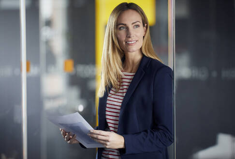 Businesswoman holding papers in office - RBF07471