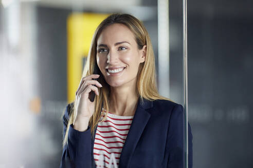 Portrait of smiling businesswoman on the phone in office - RBF07474