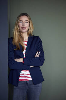 Portrait of confident businesswoman leaning against a wall - RBF07486