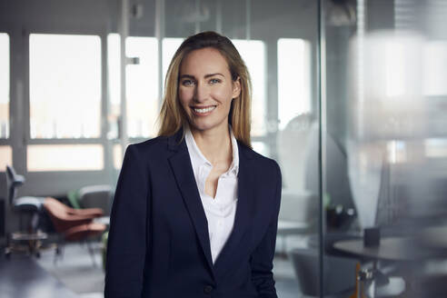 Portrait of smiling businesswoman in office - RBF07513