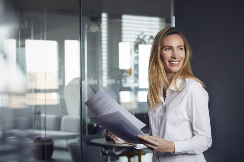 Smiling businesswoman holding papers in office - RBF07519