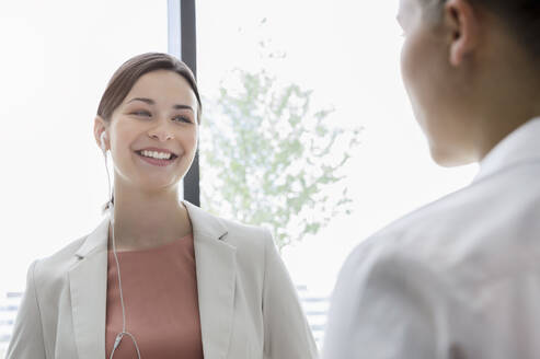 Portrait of smiling young businesswoman with earphones and colleague in office - BMOF00383