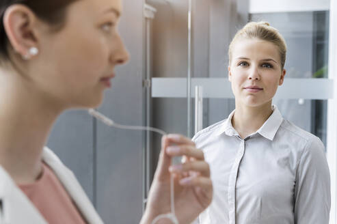 Portrait of confident young businesswoman with colleague in office - BMOF00389