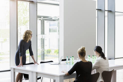 Businesswomen having a meeting in bright office - BMOF00395
