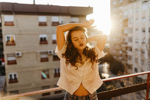 Portrait of beautiful young woman on balcony at sunset - TCEF00454