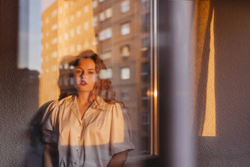 Portrait of beautiful young woman behind windowpane at home - TCEF00457