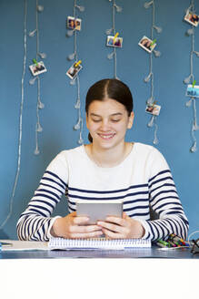 Portrait of smiling girl sitting at desk at home looking at digital tablet - LVF08758