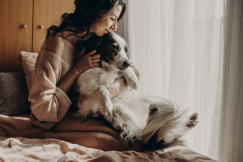 Happy woman sitting on bed at home stroking her dog - GMLF00001