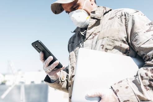 Soldier with face mask on emergency operation, using smartphone, carrying laptop - JCMF00567