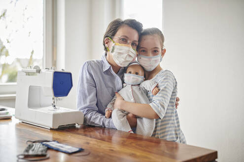 Little girl and her doll, wearing face masks, her mother has made for them - DIKF00427