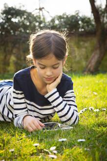 Portrait of little girl lying on a meadow using digital tablet - LVF08771