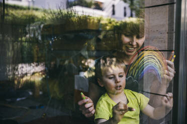 Mother and little son at home drawing rainbow on the window - MFF05415