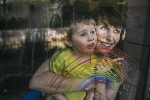Portrait of happy mother and her little son looking out of window with drawn rainbow - MFF05418
